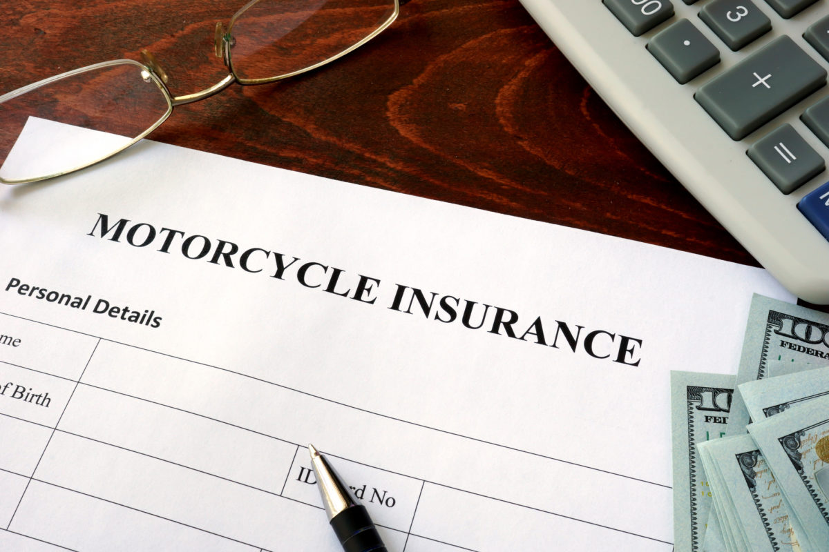 Motorcycle insurance form and dollars on the table.
